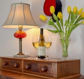 View of the dresser top with a lamp, wine bottle and glasses and a vase of yellow tulips.