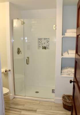 White subway tiled shower with glass doors and decorative tile cutout for amenities, side shelves with bathrobes and towels, tiled floor