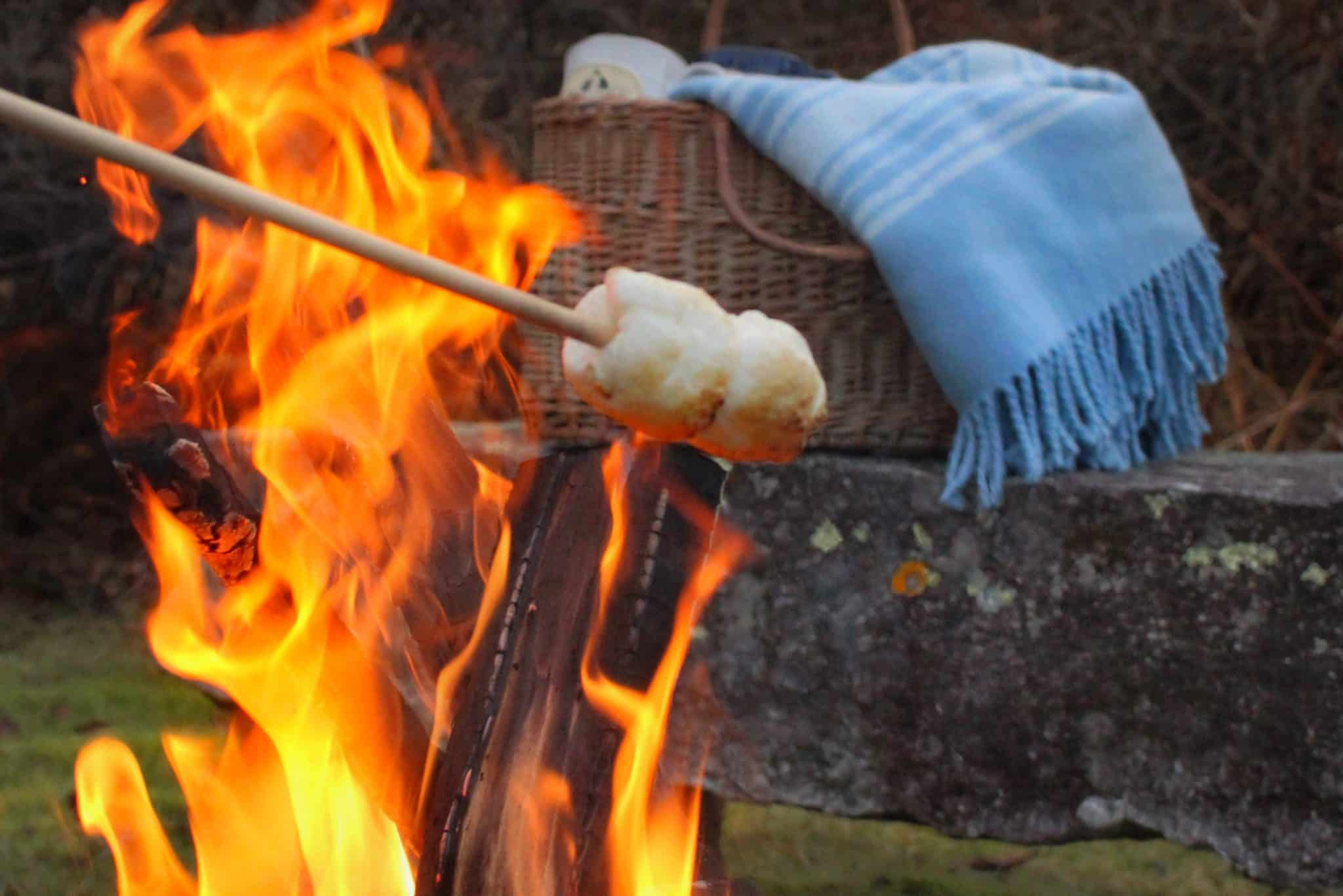 Close up of a stick with marshmallows over a fire with a bench, basket and blue blanket in the background