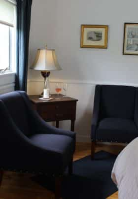 Bright room, pale grey and white walls, with two navy blue chairs, a corner table with a lamp and wine with two glasses