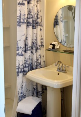 View into the bathroom with a walk in shower, white shower curtains with navy blue tall ships, pedistal sink, mirror with shelf containing amenities