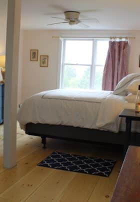 view of the room from the door, wide plank pine flooring, king bed with crisp white linens with navy trim, blue dresser and window