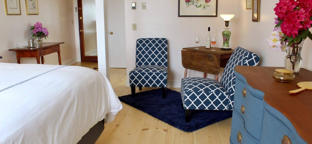 Beautiful wide plank pine flooring with a corner seating areas with two navy blue slipper chairs, a drop leaf table with antique lamp wine bottle and glasses, side table across the room with flowers, blue chalk painted dresser with brass hardware and wood top with flowers in a vase and a corner of the king bed