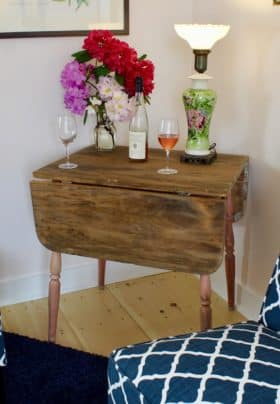 Cozy corner with Blue slipper chairs, drop leaf table, antique lamp, flowers with wine bottle and glasses.