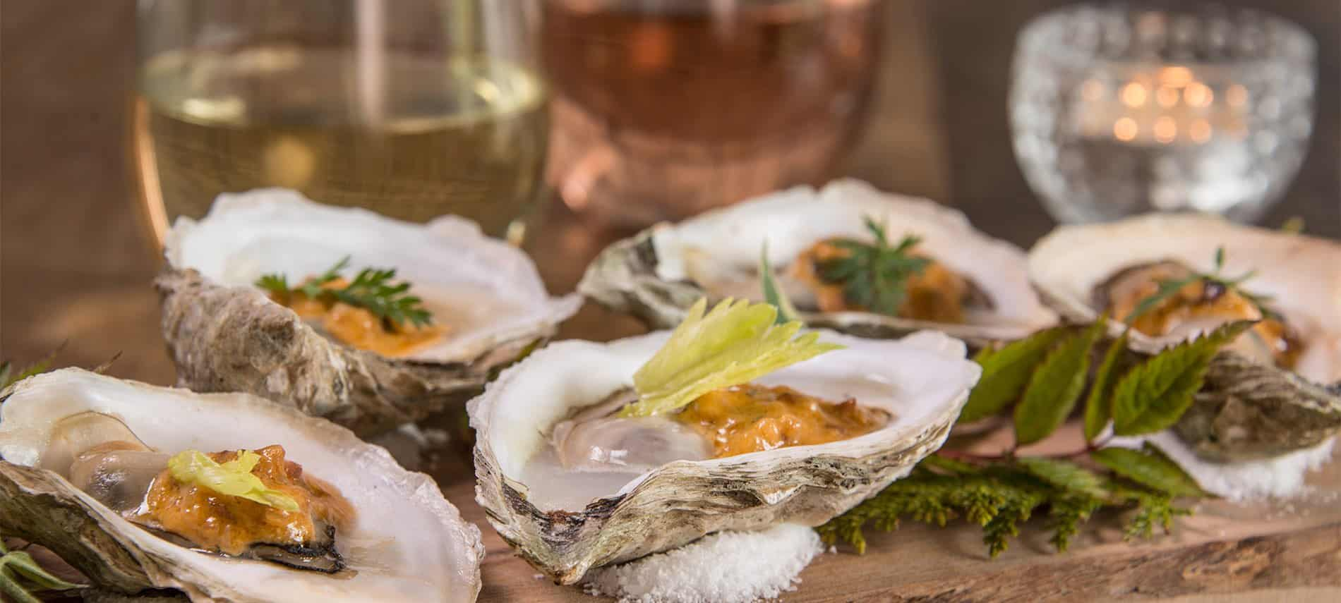 Oysters in shells with fresh herbs and two glasses of wine .