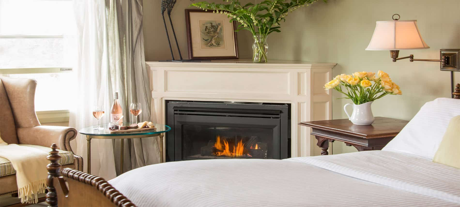 Antique bed with white duvet, tan wingback chair, and roaring fireplace.