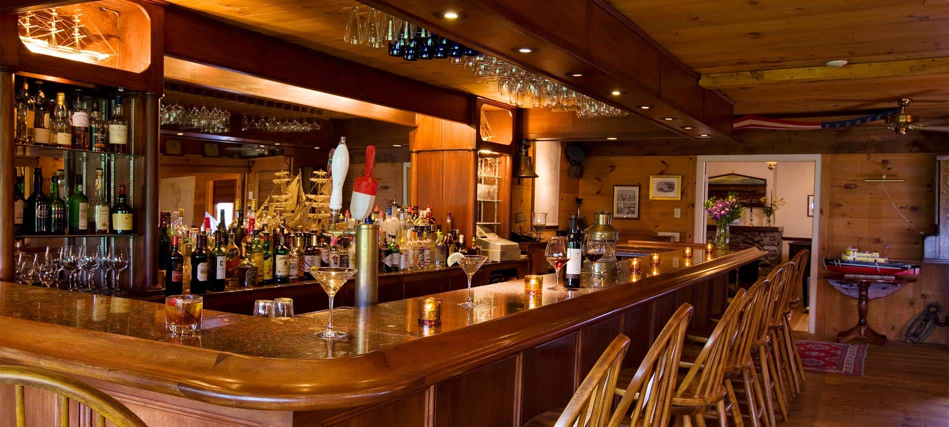 Oak bar with several wooden chairs, glasses and various liquers behind the counter.