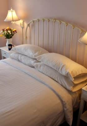 Pale lavender walls, with a queen bed with a white iron head board, crisp white linens and a warm glos from the side lamps with flowers and Bradley inn mugs on tables