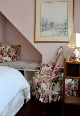 Pale lavender walls, large water color of The Bradley Inn over a floral corner chair and built inn under the cutout in the wall.