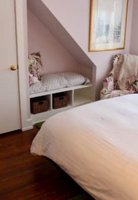 Pale lavender walls with the bed, corner chair and builtin under the cutout in the wall.