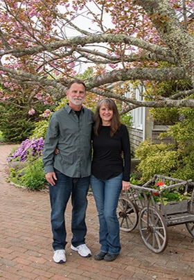 Photo of ownswer of the inn in front of small wooden cart, large tree, and purple flowering busch.