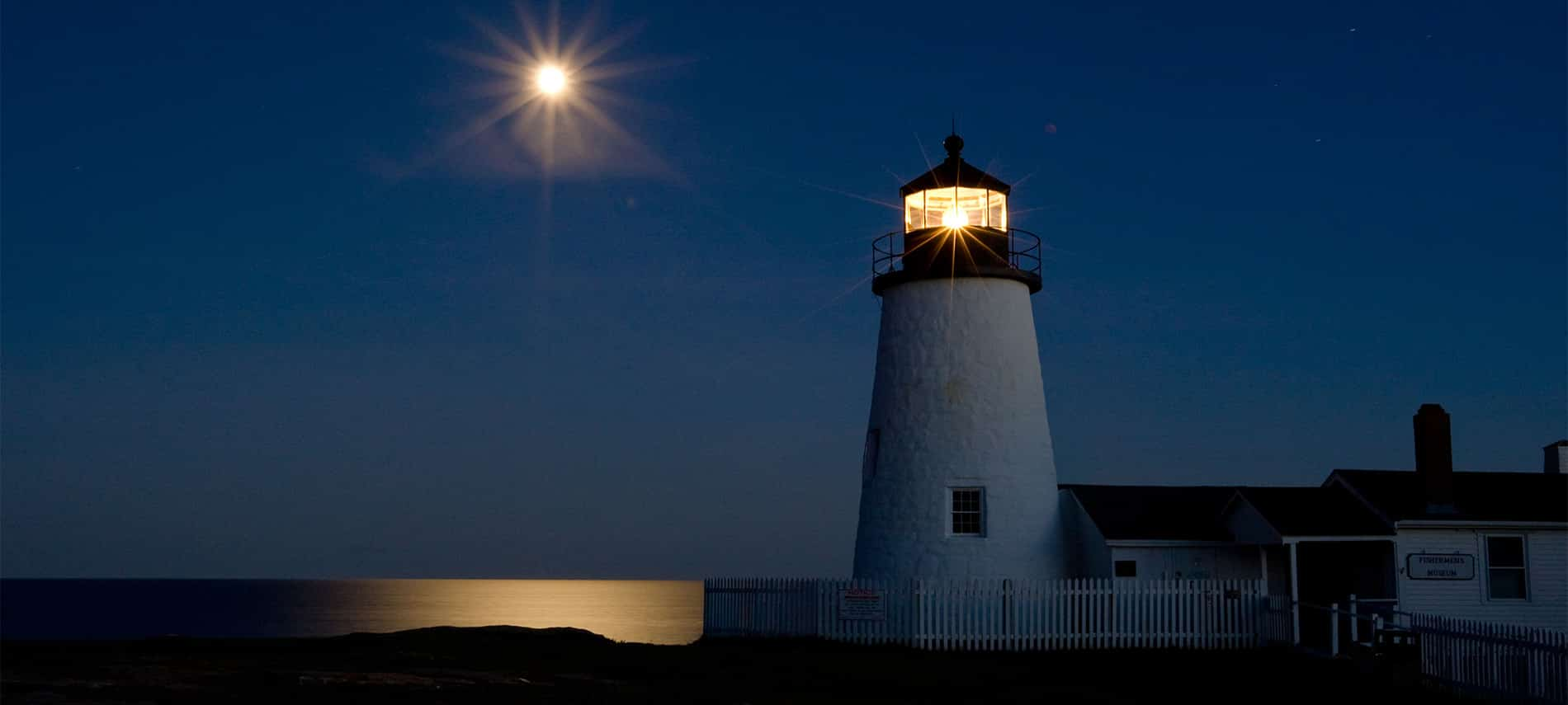 Blue night sky with glowing moon shining on the water and lit up lighthouse .