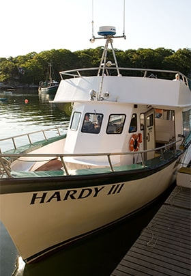White boat with the name Hardy III sitting beside a wodden dock.