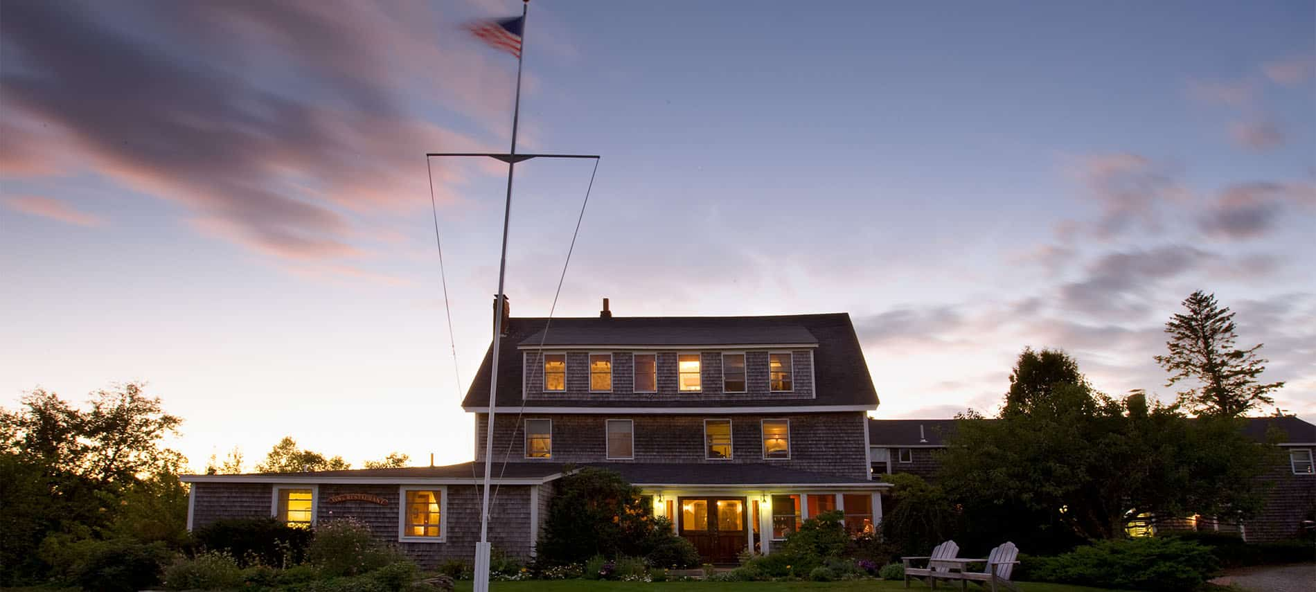 Outside of grey house with several windows and a US flag flying.