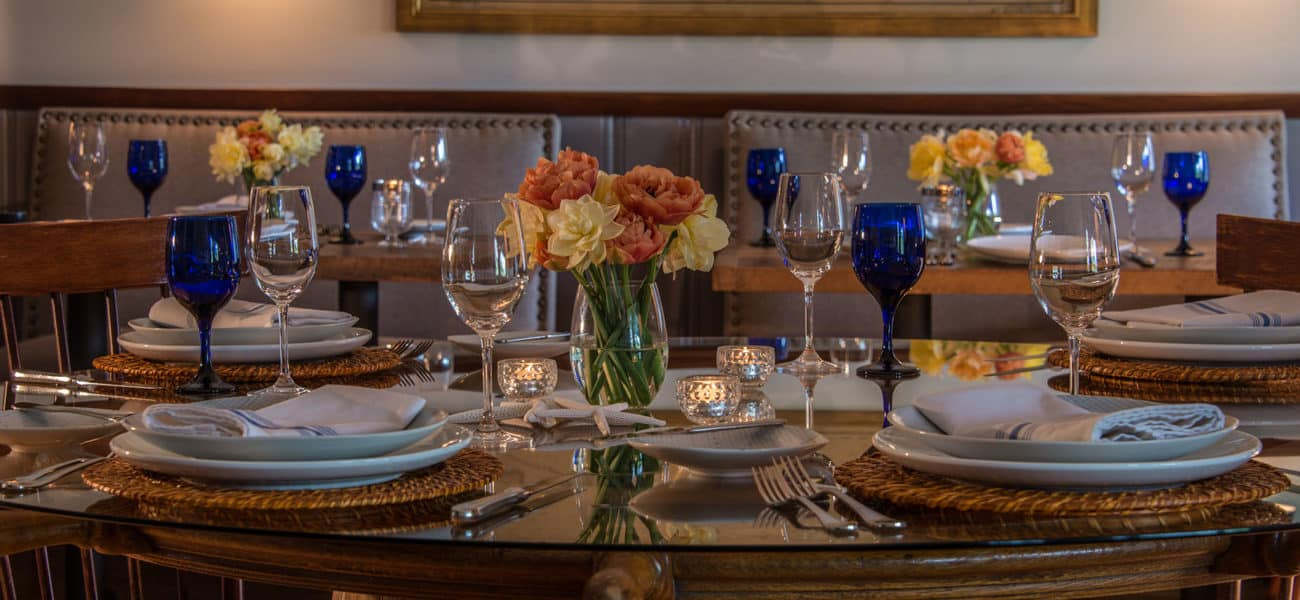 Table with white plates, blue stemware, complete place settings, and orange and yellow flowers.