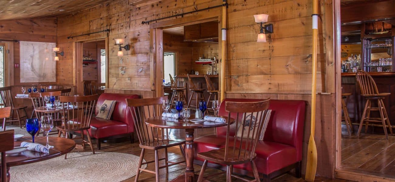 View of the side room of the tavern with red leather banquet benchs, wooden tables and chairs. Room is entirely paneled with wide plank pine boards creating a warm atmosphere. Tables are set with blue water goblets, wine glasses, napkin rollups and plates