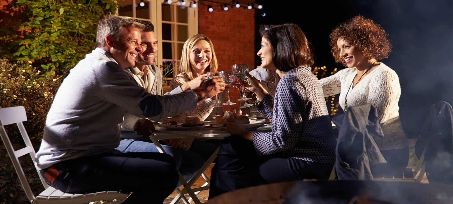 Two couples sitting around a firepit on a porch with lights around the trees.