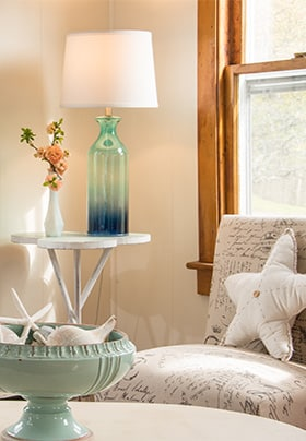 Grey chair with star shaped pillow in front of window with blue lamp on side table.