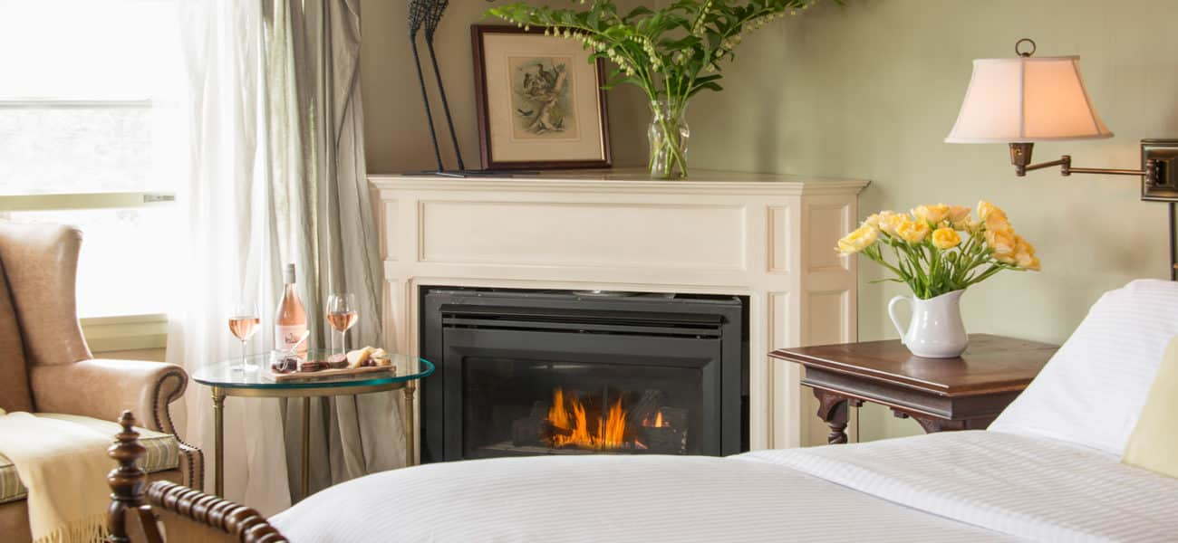 Fireplace with yellow flowers, tan wingback chair, and bed with white duvet.