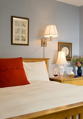 Oak bed with white duvet, light blue walls, red pillow, and wall lamp.