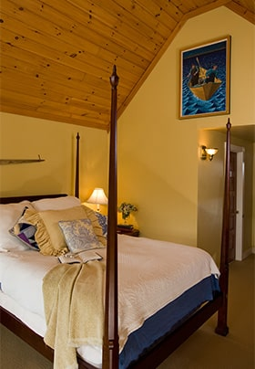 Four poster bed with blue and white bed spread and gold throw, oak wood cieling and gold walls.