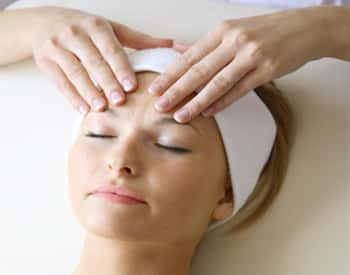 Woman getting a facial and head massage with a white cloth on her head.