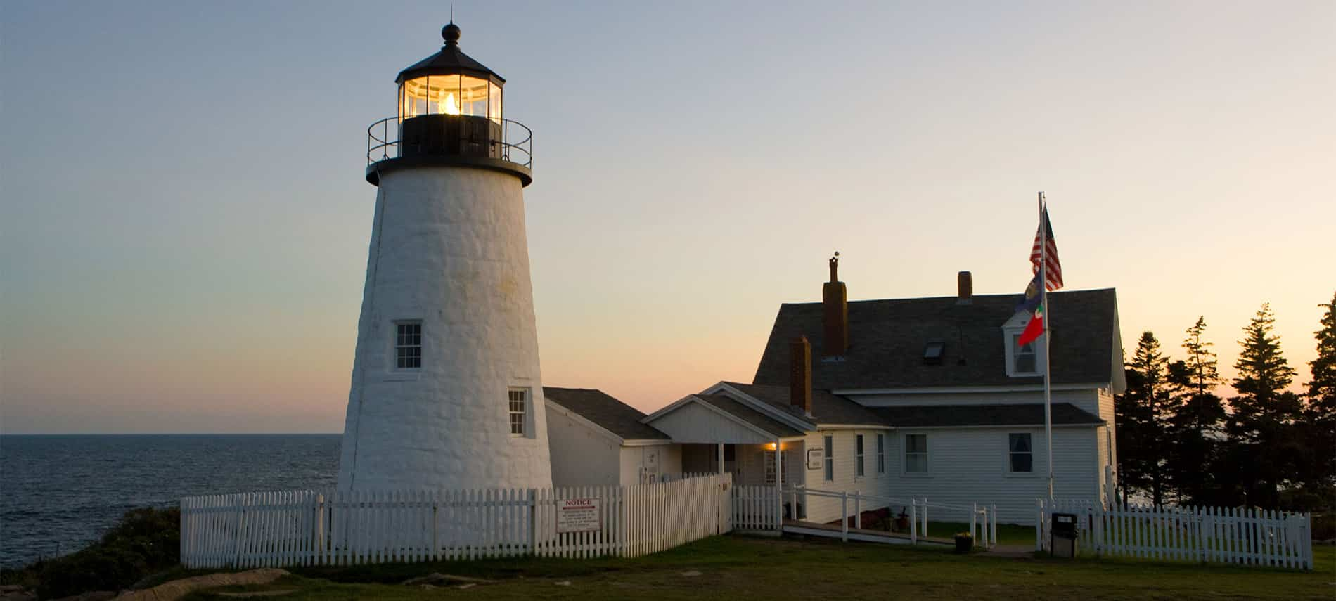 Large, white, light house that is lit up with white inn attached that has a american flag and a beautiful sky behind it.