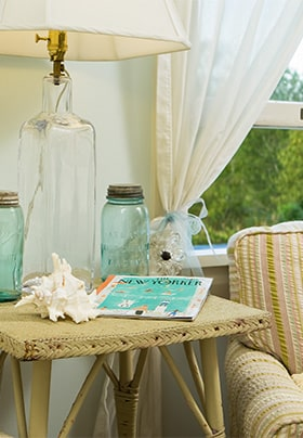 Cloth chair with blue glas mason jars and shells on a table.
