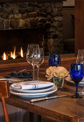 diningroom table looking towards the hall fireplace with is burning brightly, table is set with dishes, napkings, silverware, sparkling wine and blue water glasses. a small vase of flowers is in the middle of the table.