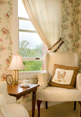 Cream wingback chair with floral wallpaper in front of chair with sheer curtains.